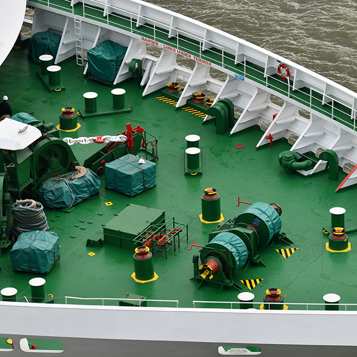 Close up of front deck of ship showing deck furniture on green background and part of the bow
